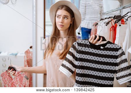 Thoughtful confused young woman choosing between two dresses in clothing store
