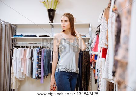 Portrait of pretty young woman doing shopping in clothing store