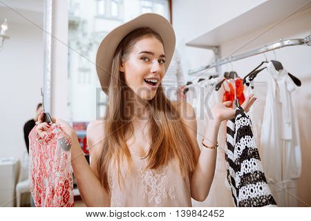 Cheerful young woman in hat choosing clothes in clothing store