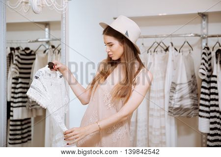 Pensive cute young woman in hat choosing and looking at dress in showroom