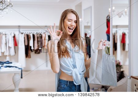 Cheerful young woman with shopping bag winking and showing ok sign in clothing store