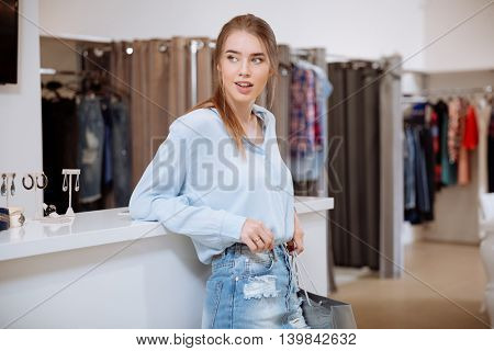 Relaxed happy young woman with shopping bag standing in clothing store