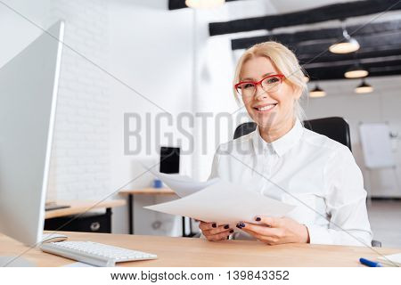 Attractive mature woman holding a sheet of paper and posing while sitting at the office
