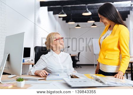 Two smiling businesswomen working together on the notebook at the table in office