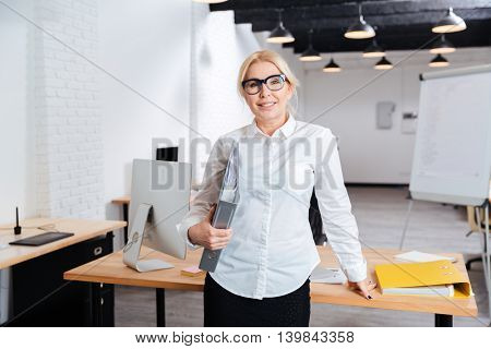 Happy businesswoman standing and holding folders leaning on desk at the office