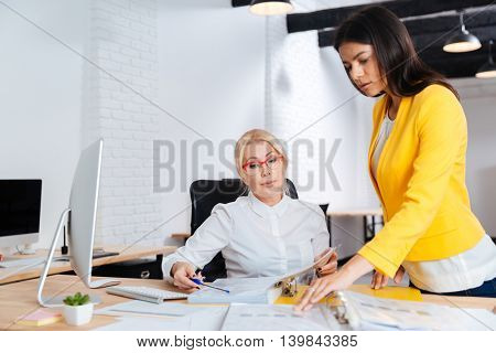 Two young and mature businesswoman having a meeting in the office