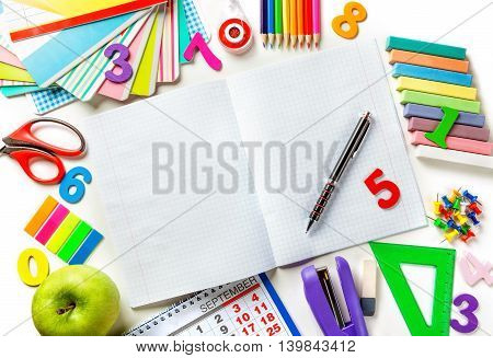 Open blank page notebook with a pen in the center of the frame with copy space. Various office supplies. Concept back to school