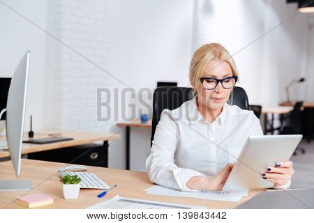 Mature attractive businesswoman working in office with pc tablet