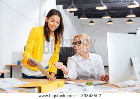 Two smiling businesswomen working together with pc at the table in office