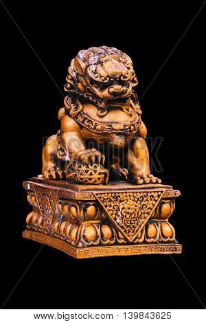 Chinese golden lion statue isolated on black background.