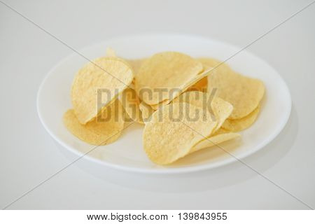 snack food of potato chips crispy  in white ceramic bowl  on white background
