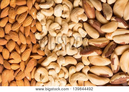 Almonds Cashew and Para Nuts over a wooden table