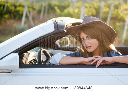 Cowboy girl sits behind the wheel of a white convertible