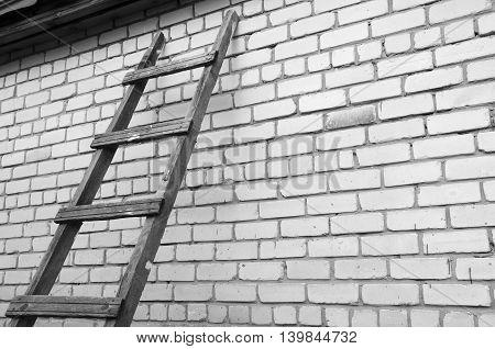 Wooden ladder sideways at a brick wall