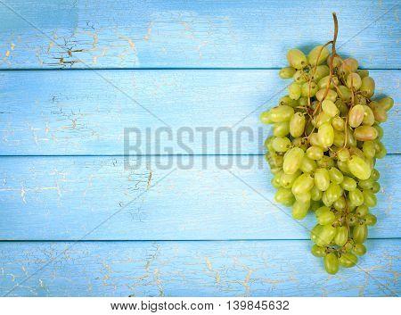 Green grape fruit on blue wooden plank background