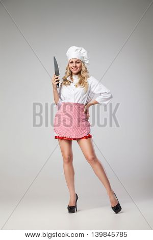 Portrait of smiling blonde woman in chef uniform holding knife.Studio shot.