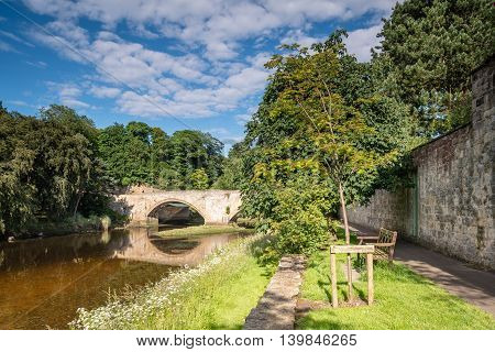 River Coquet flows under Warkworth Bridge, an old medieval bridge which is one of just two fortified bridges in Briton
