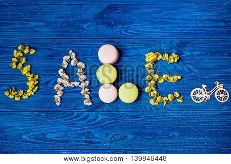 the inscription of laid flowers and macarons on wooden background, the sale text on blue wooden board