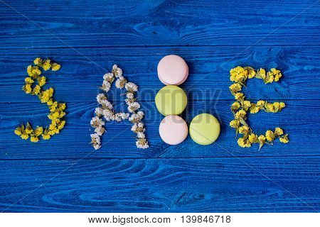 the inscription of laid flowers and macaron on wooden background, the sale text on blue wooden board