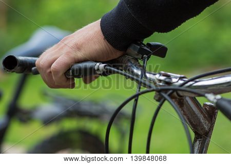 Man's hands holding handle of a cycle