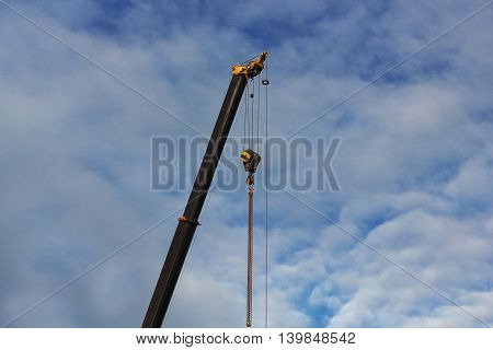 Crane and metal profile structure over blue sky photo