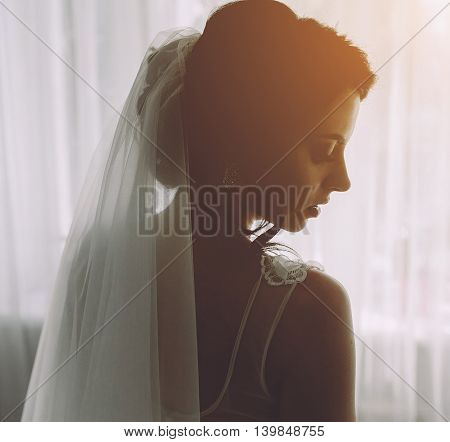 Bride posing in a large window on the camera