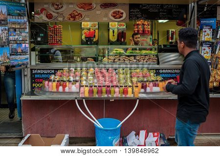 Barcelona Spain - October 26 2015: Fresh juice sliced fruits sandwiches snacks are being sold at the hot dog stand in Barcelona Spain on 26 October 2015.