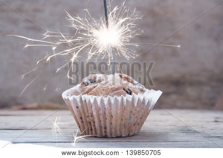 Cupcake with sparkler against brown, celebrating a birthday