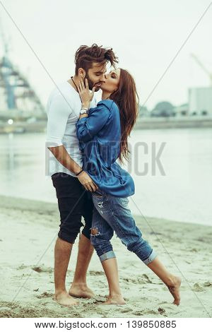 Young couple in the embrace kissing by the river