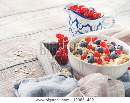 Oatmeal Porridge With Blueberries And Red Currants On Rustic Wooden Table