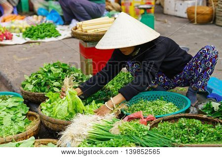 Asian Trader In A Traditional Hat Selling Fresh Greens In The Street Market
