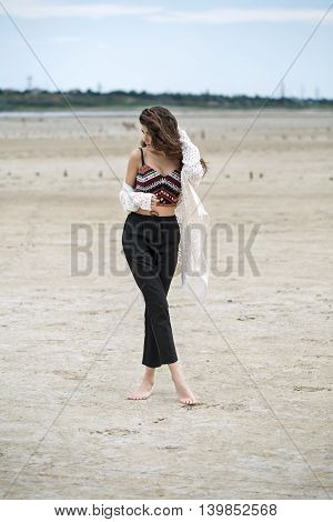 Young barefoot girl stands on the sand on the nature background. She wears black pants, multi-colored top with patterns and a white cardigan. Her legs are crossed, right hand is near the top, left hand is on the hair, head is partially turned to the right