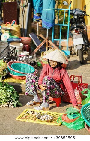 Asian Trader In Traditional Hat Selling Mushrooms And Fresh Vegetables