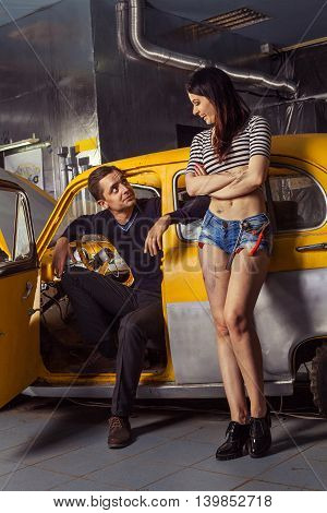 Woman Mechanic In Sexy Shirts Is Listening The Complains Of The Owner Of An An Old Car.