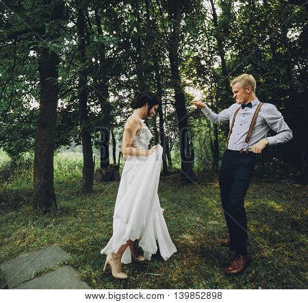 bride and groom dancing in nature, somewhere in the forest