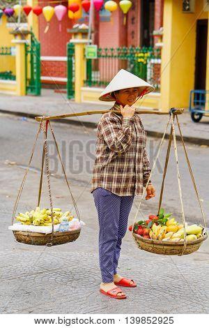 Asian Woman Seller Carrying Rambutan Mango And Banana