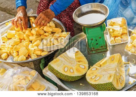 Asian woman selling flesh of fresh durian fruit just cleaned and packed in the street in Hoi An Vietnam.