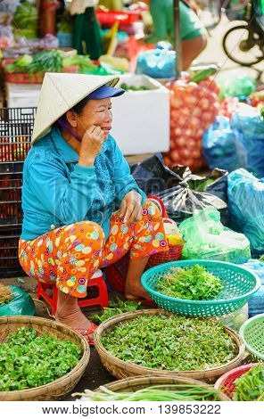 Asian Woman Trader Selling Fresh Greens In The Street Market