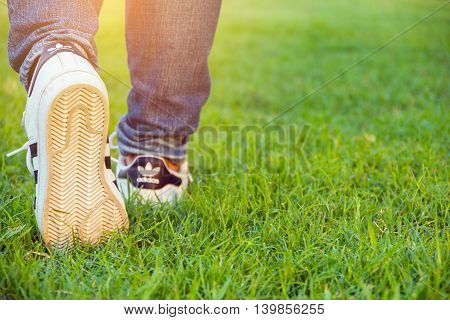 Bangkok Thailand - July 25 2016 : Woman walking with Adidas superstar shoes on green grass