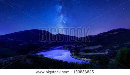 night sky stars on mountain lake. Milky way reflections in dark water