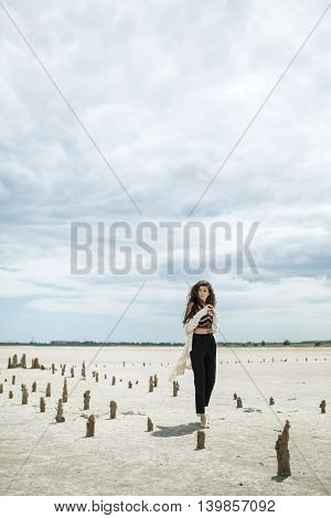 Gorgeous barefoot girl walks on the sand on the cloudy sky background. She wears black pants, multi-colored top with patterns and a white cardigan. She holds her hands together in front of herself. She looks to the side. There are wooden pillars on the sa