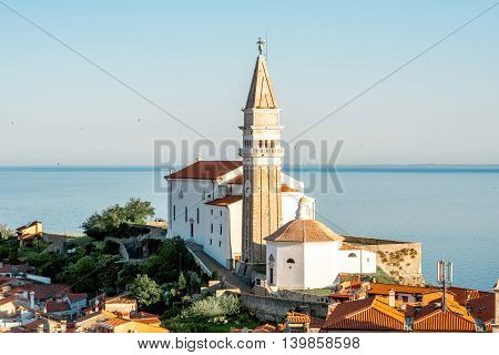 Aerial city scape view on Piran town with church tower and Adriatic sea on the background in Slovenia