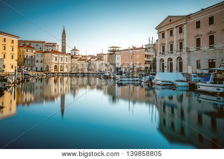 View on Piran medieval town from the bay with boats at the sunrise in Slovenia