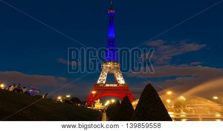 Paris France-July 16 2016 : The Eiffel tower lit up with colors of French national flag to honor the victims of July 14 2016 terrorist's attack in Nice.
