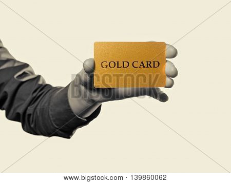Black and white toned photo a hand with gold card on a isolated background