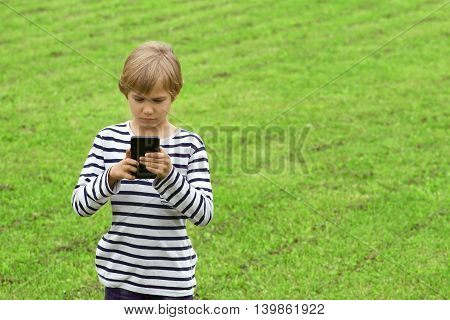 Boy with mobile phone outdoor. Child looking at the screen, playing, using apps. Green grass background. People, technology, leisure concept