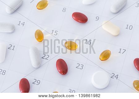 Close-up of pills on a daily and weekly calendar schedule
