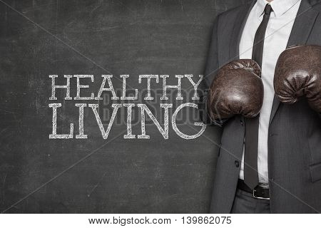 Healthy living on blackboard with businessman wearing boxing gloves