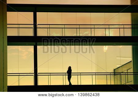 Silhouette view of young businesswoman in a modern office building interior with panoramic windows.