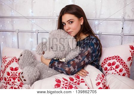 girl playing with teddy bear in bed
